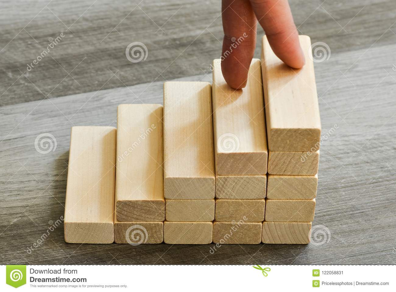 Success Concept - Fingers Climbing Up To Top Of Stairway Over Dark Wooden Background