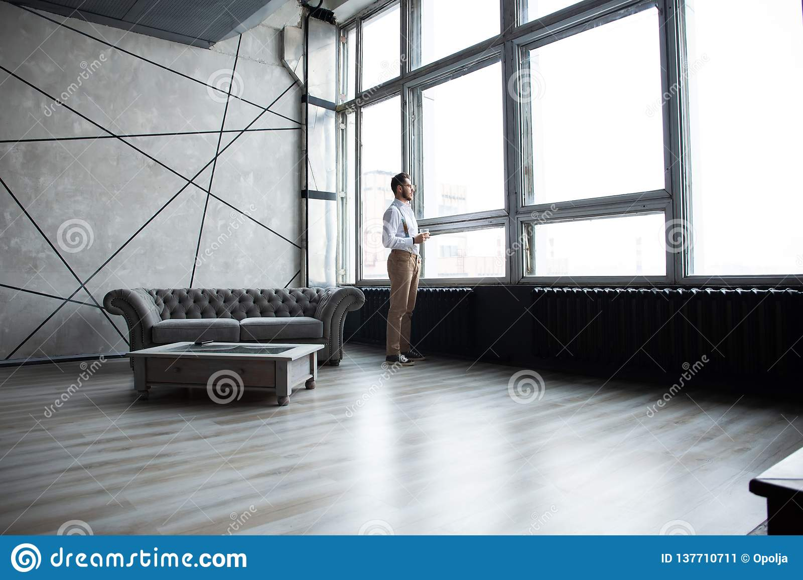 Success concept. Stylish young bearded man is standing near the window and looking far. He is in a suit, pensive and