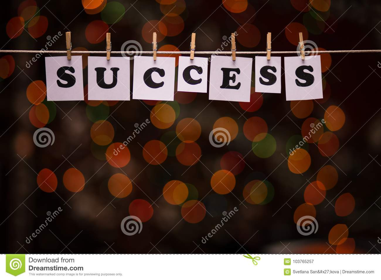 Success text on papers with clothespins with garland bokeh on background