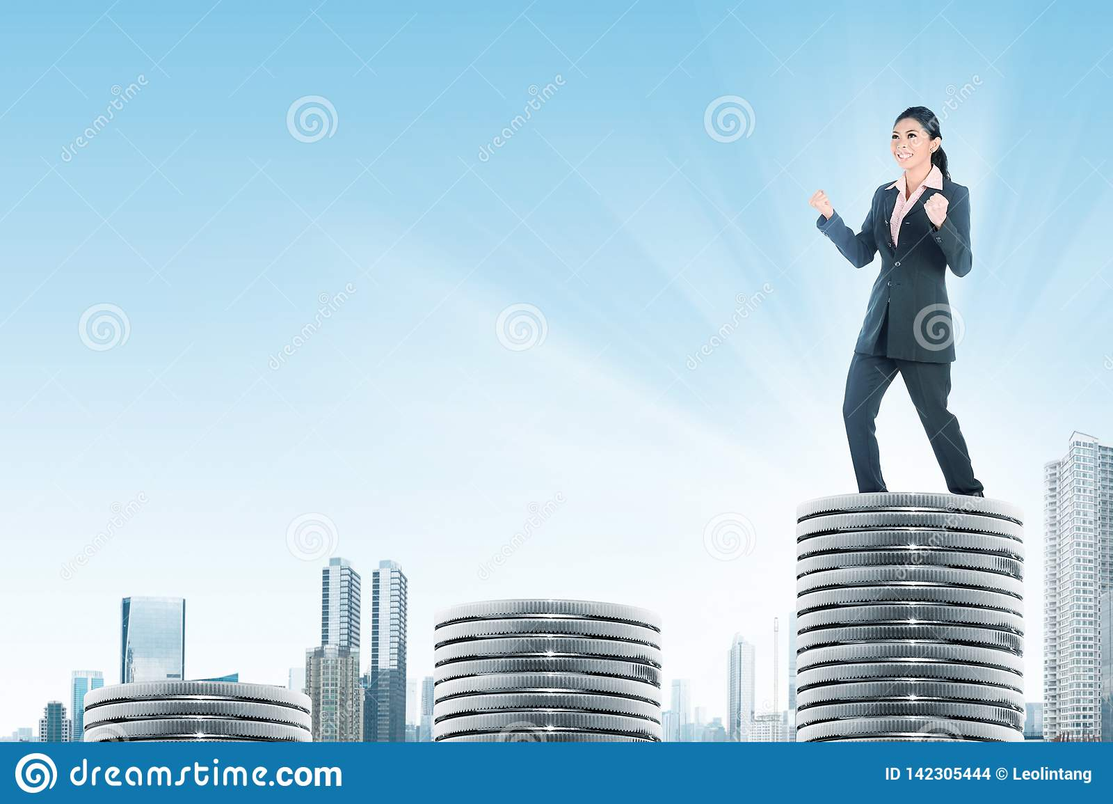 Successful asian business woman standing on the highest silver coins
