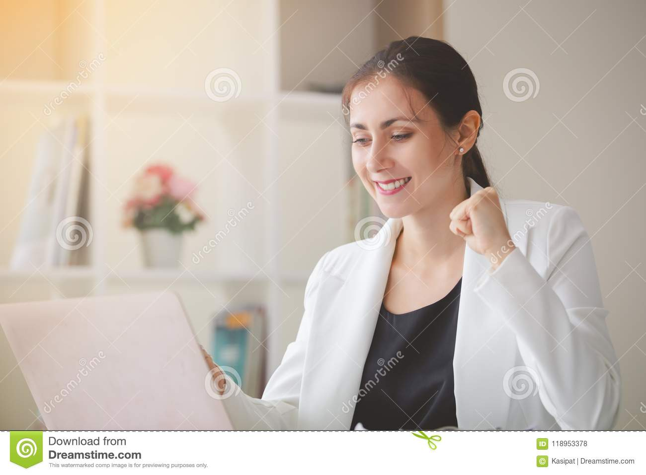 Successful business woman looking laptop with arms up