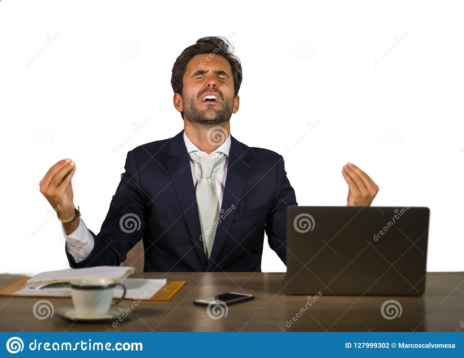 Successful handsome businessman in suit working at office computer desk celebrating financial success winning money smiling cheerf