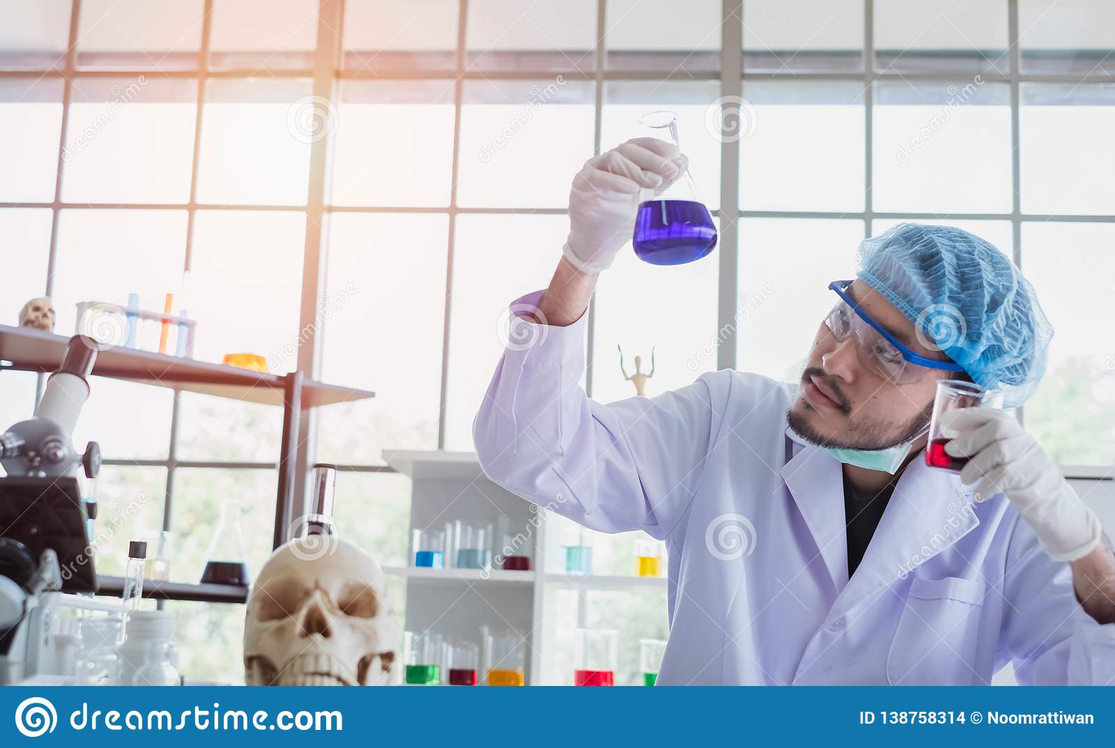 A successful male chemist is examining his new innovation in a laboratory.
