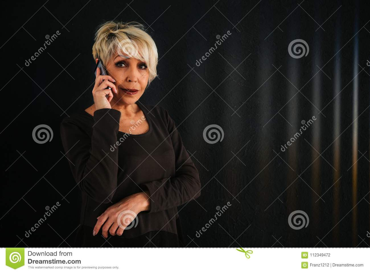 A successful positive elderly female consultant is negotiating a cell phone. Communication between people using modern