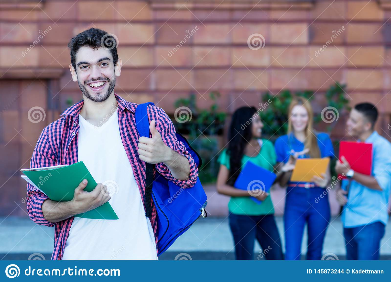 Successful spanish male student with group of students