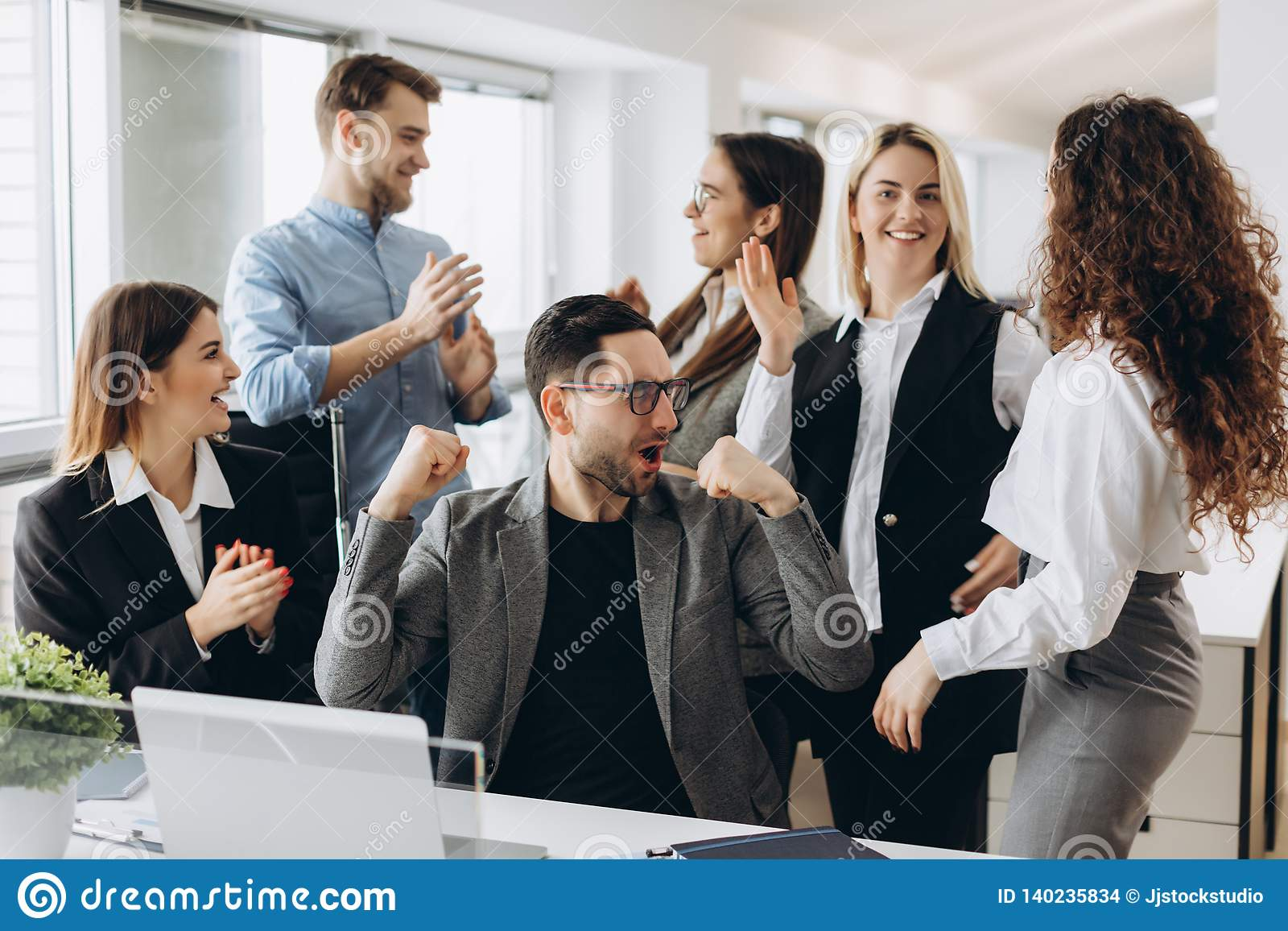 Successful young business people are raising hands in fists and screaming with happiness while working with a computer in business