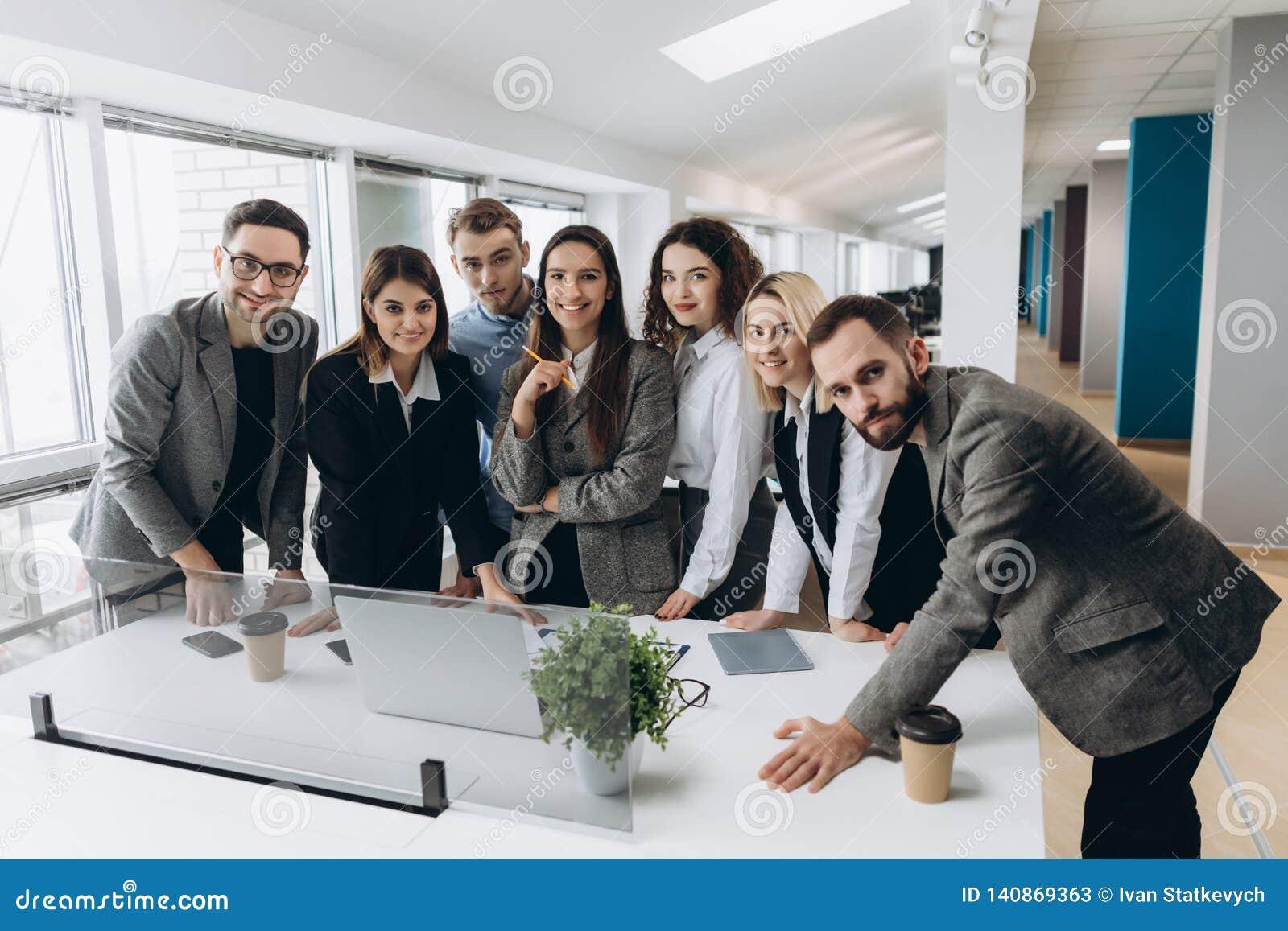 Succesvol team op het werk Groep jonge bedrijfsmensen die en in creatief bureau samenwerken communiceren