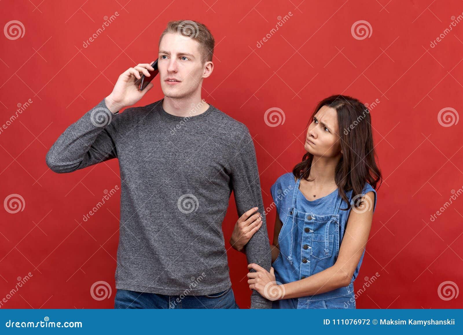 Succesvolle bedrijfsmens die op de telefoon voor zeer belangrijke kwesties spreken Zijn mooi gekwetst en ongelukkig meisje