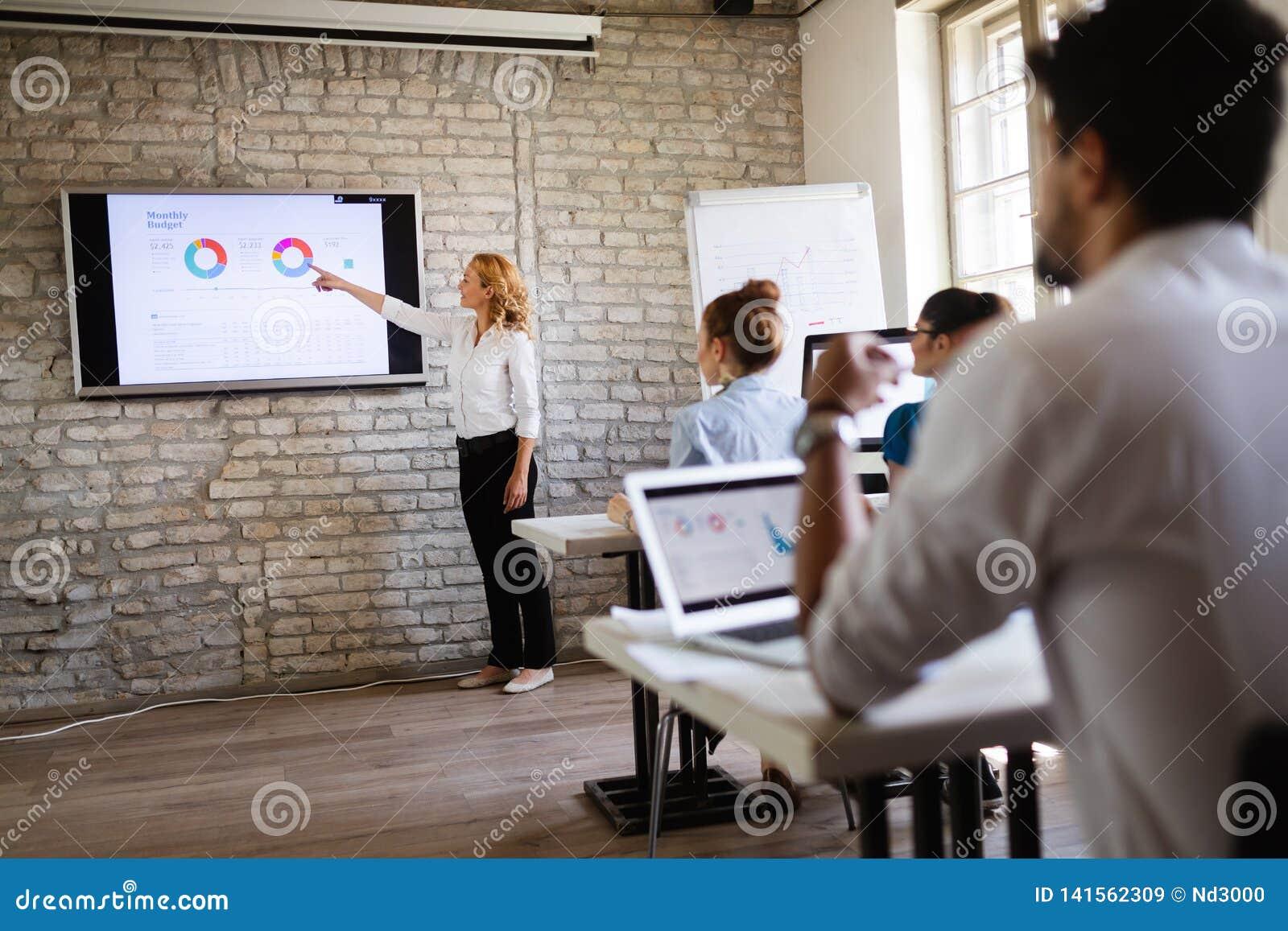 Succesvolle gelukkige groep die mensen softwaretechnologie en zaken leren tijdens presentatie
