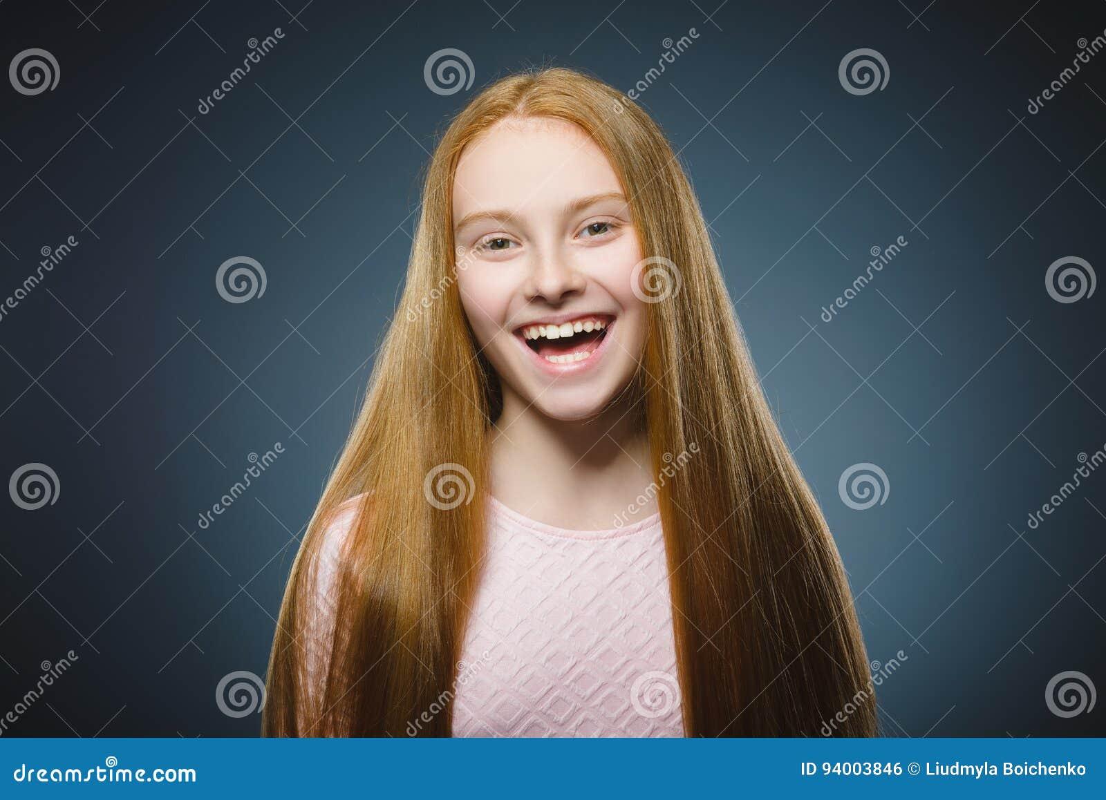Succesvolle gelukkige het meisjes grijze achtergrond van het close-upportret