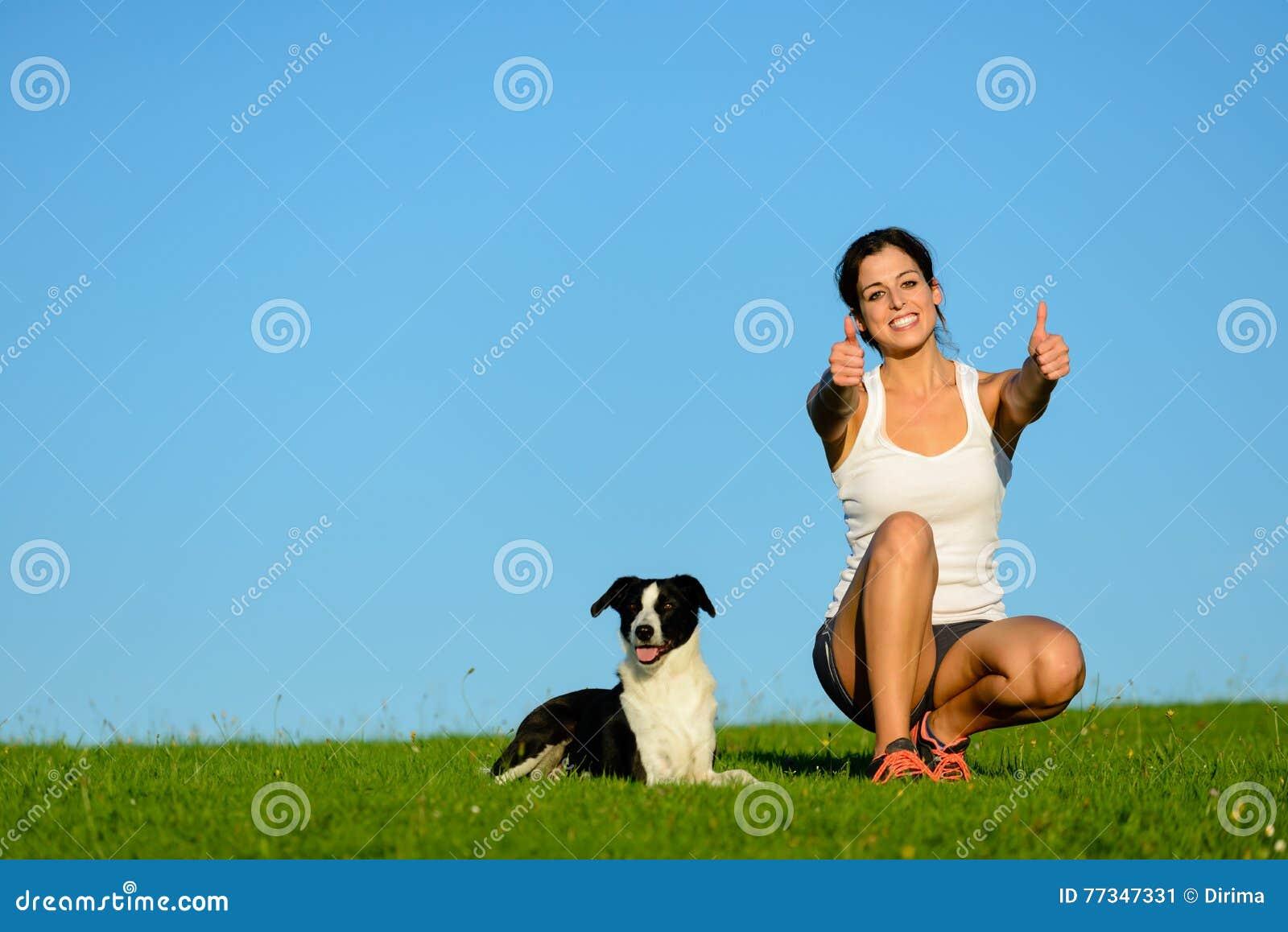 Succesvolle sportieve vrouw die een het uitoefenen rust met haar hond nemen
