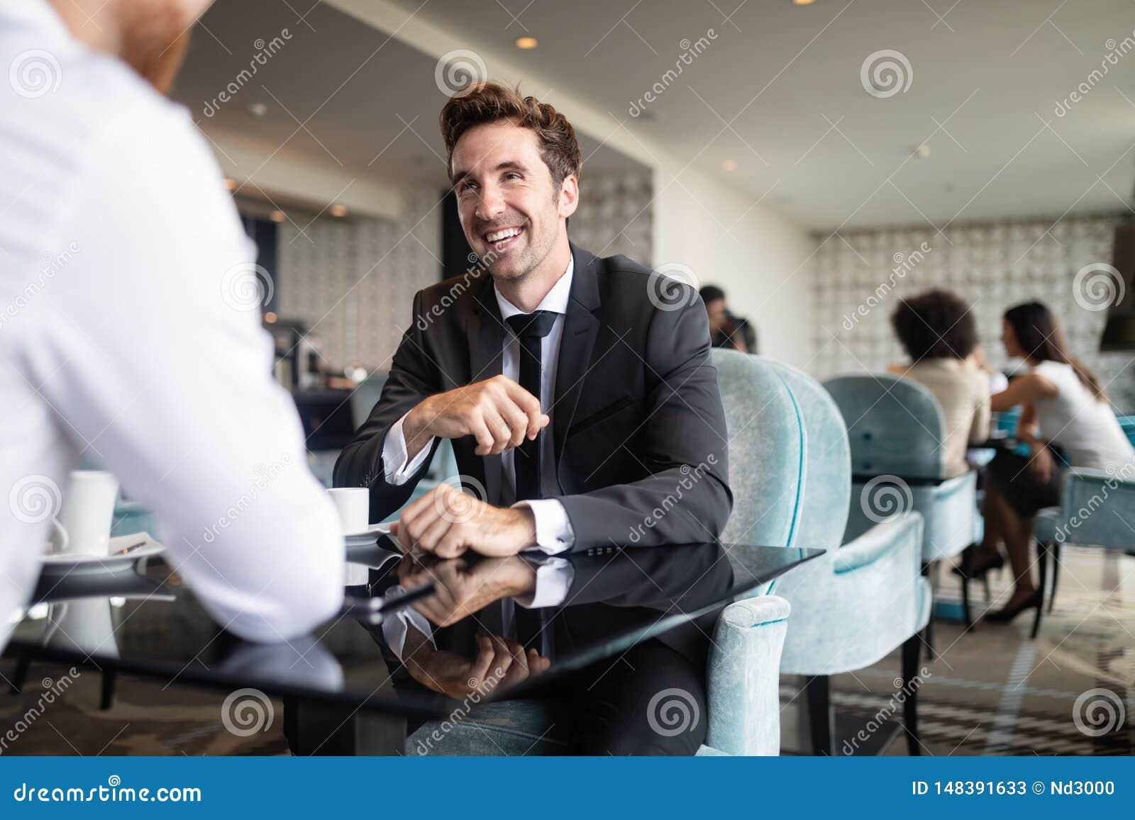 Succesvolle zakenman die terwijl het bespreken met partner tijdens vergadering bij koffiepauze glimlachen