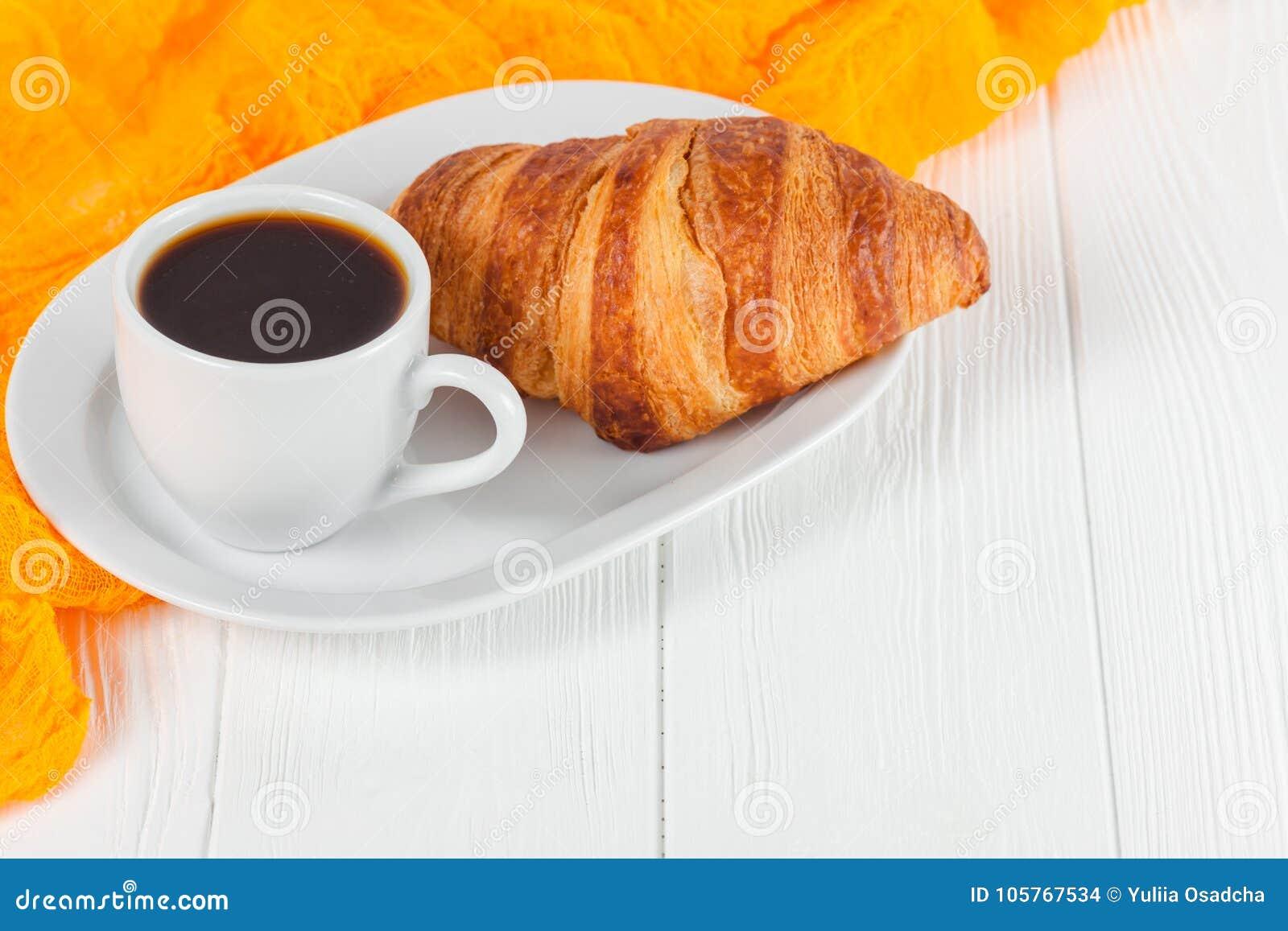 Succo d arancia di recente al forno del croissant, inceppamento, tazza di caffè nero su fondo di legno bianco Pasticcerie fresche