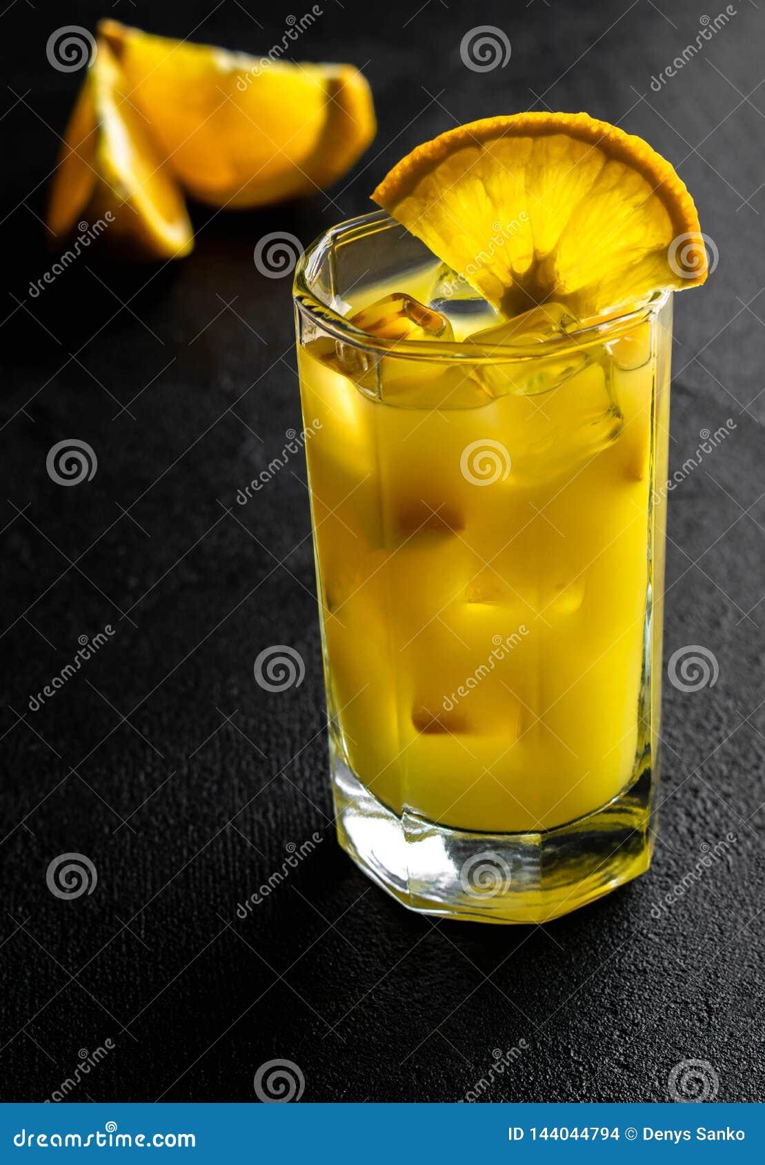Succo d arancia di vetro con ghiaccio e fette arancio su fondo nero