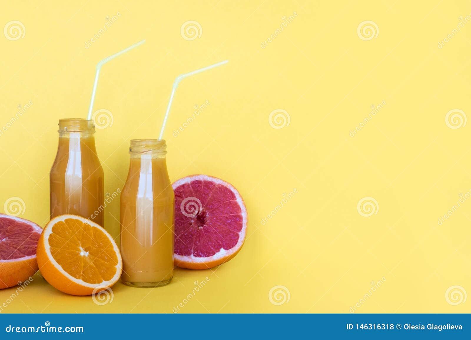 Succo d arancia fresco in bottiglie con le arance su fondo giallo Copi lo spazio