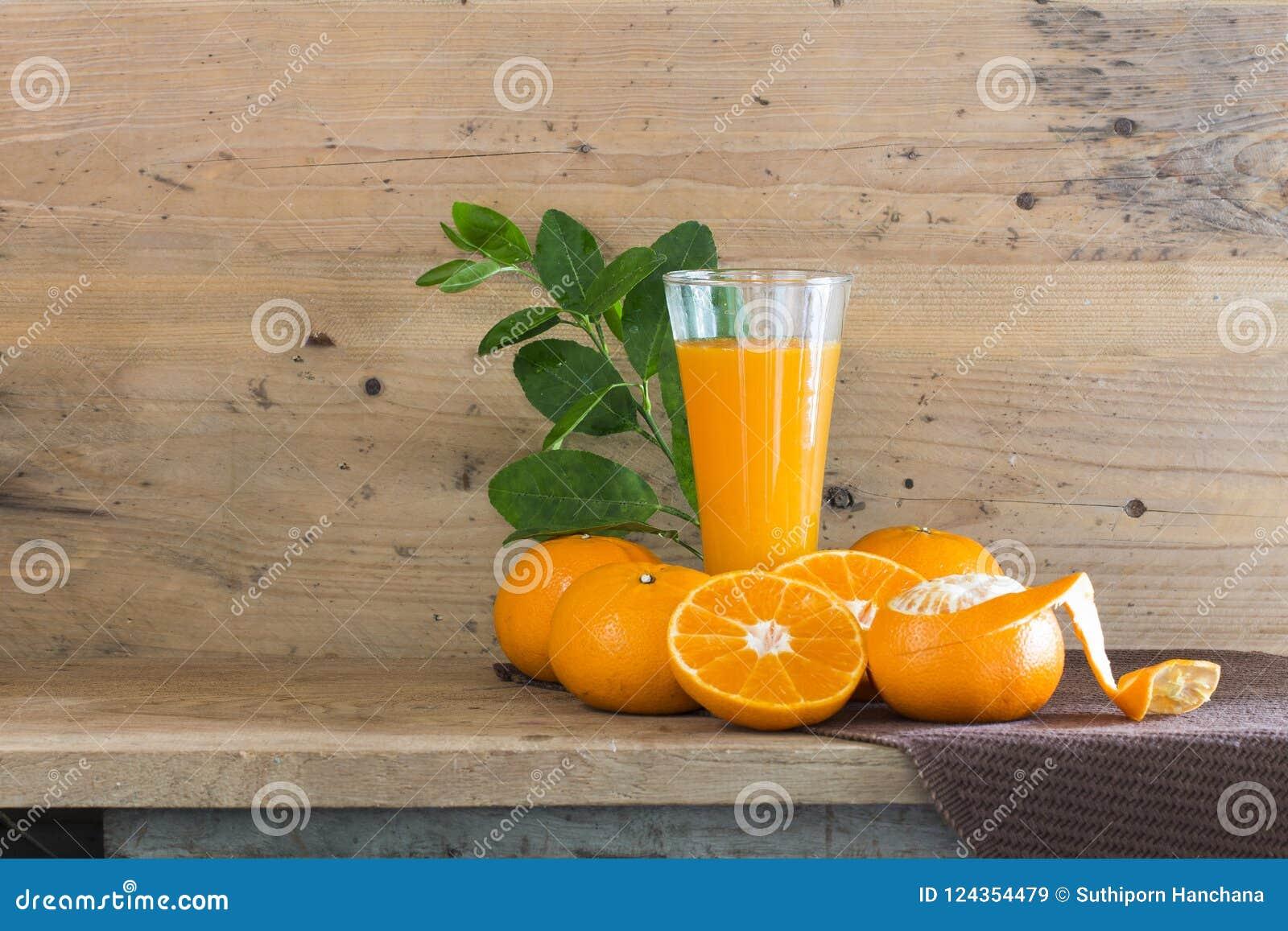 Succo di arancie fresco in vetro su legno a creativo per progettazione