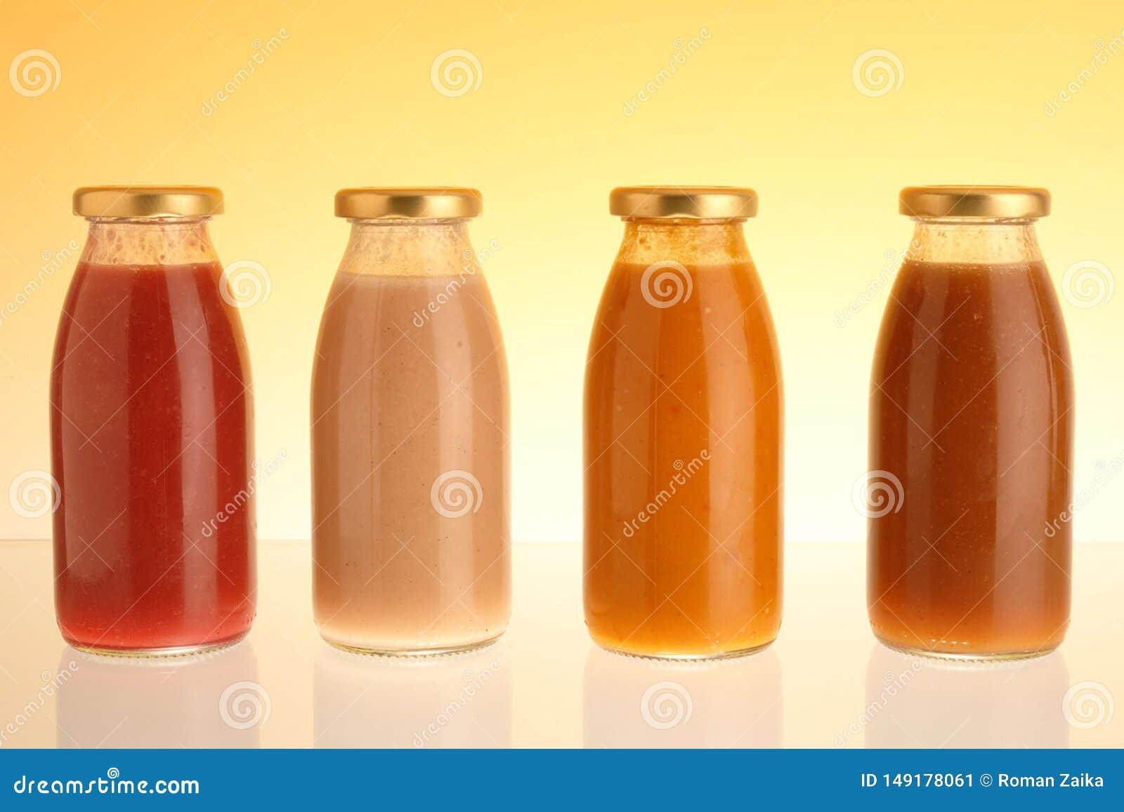 Succo di mela, della pesca, della carota e della prugna in una bottiglia di vetro