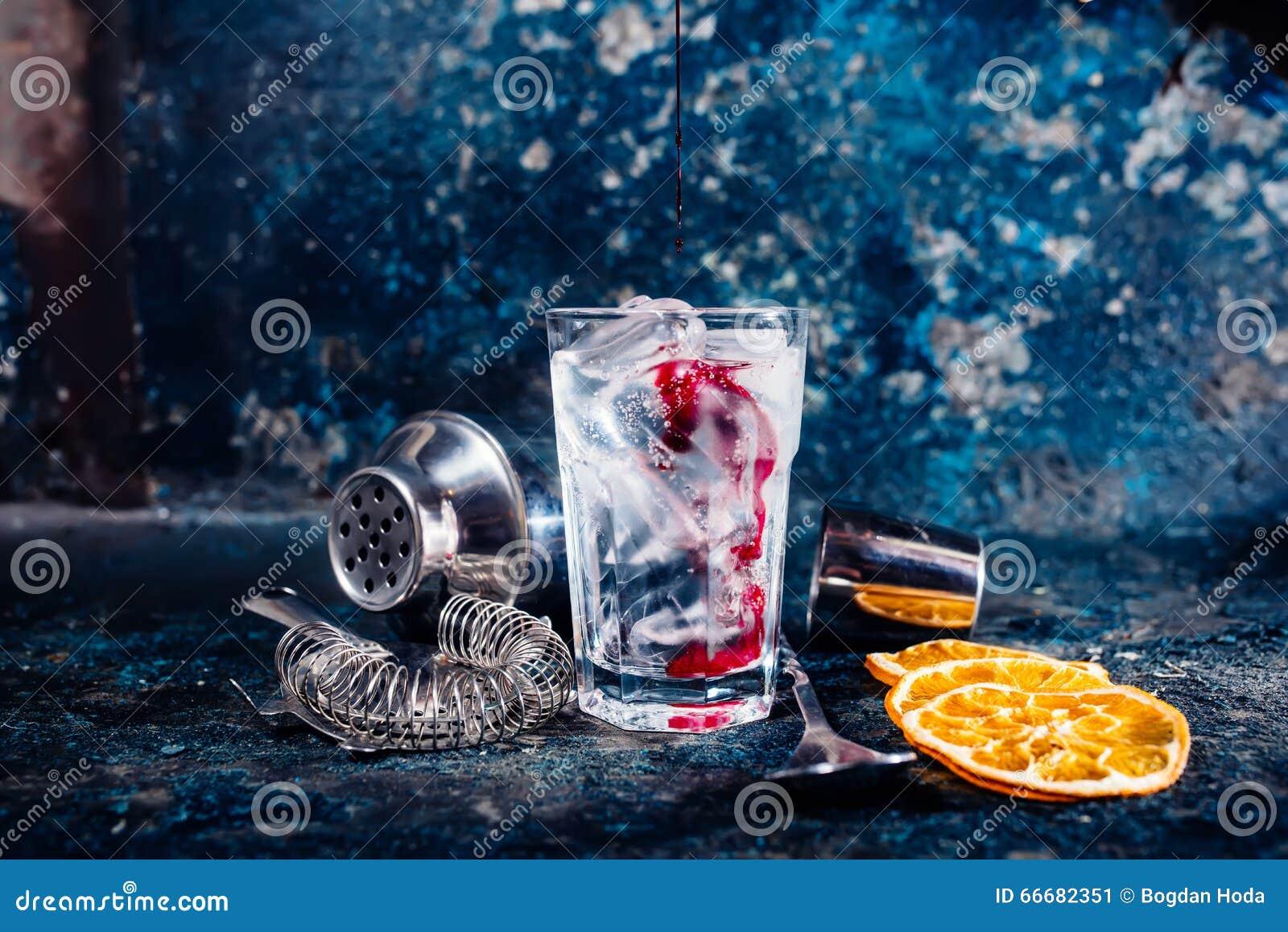Succo di mirtillo rosso di versamento del barista sopra il cocktail della vodka