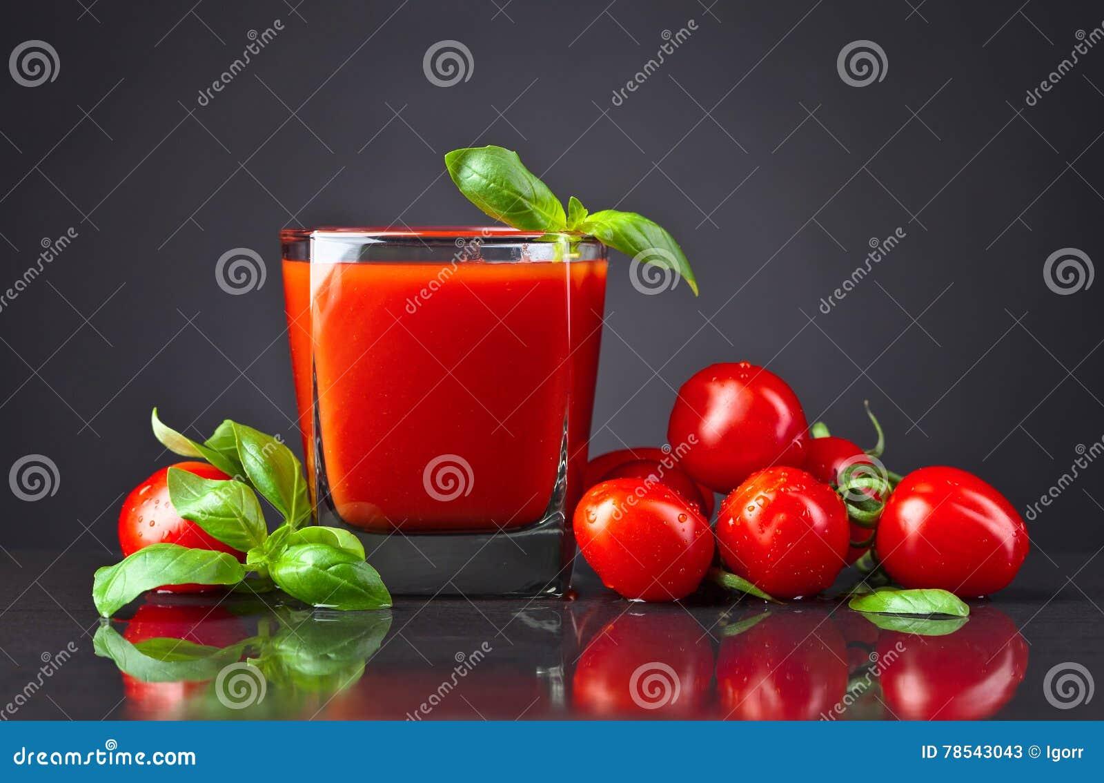 Succo di pomodoro con i pomodori e basilico verde sulla tavola nera
