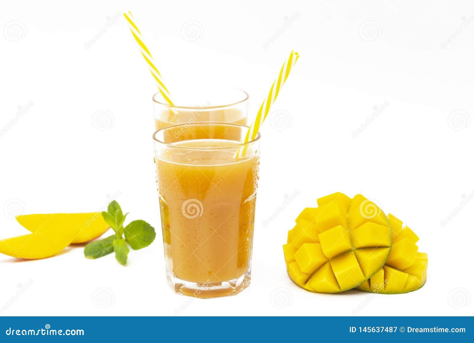 Succo fresco del mango del frullato della frutta tropicale e mango fresco su un fondo bianco
