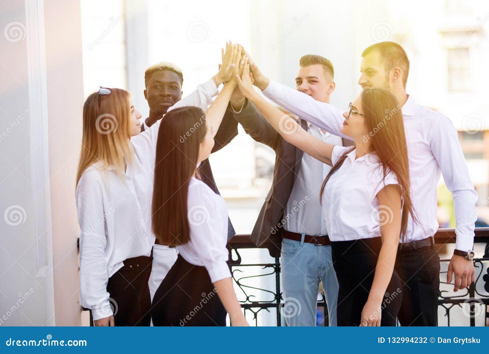 Sucesso e conceito de vencimento Equipe feliz do negócio que dá a elevação cinco no escritório