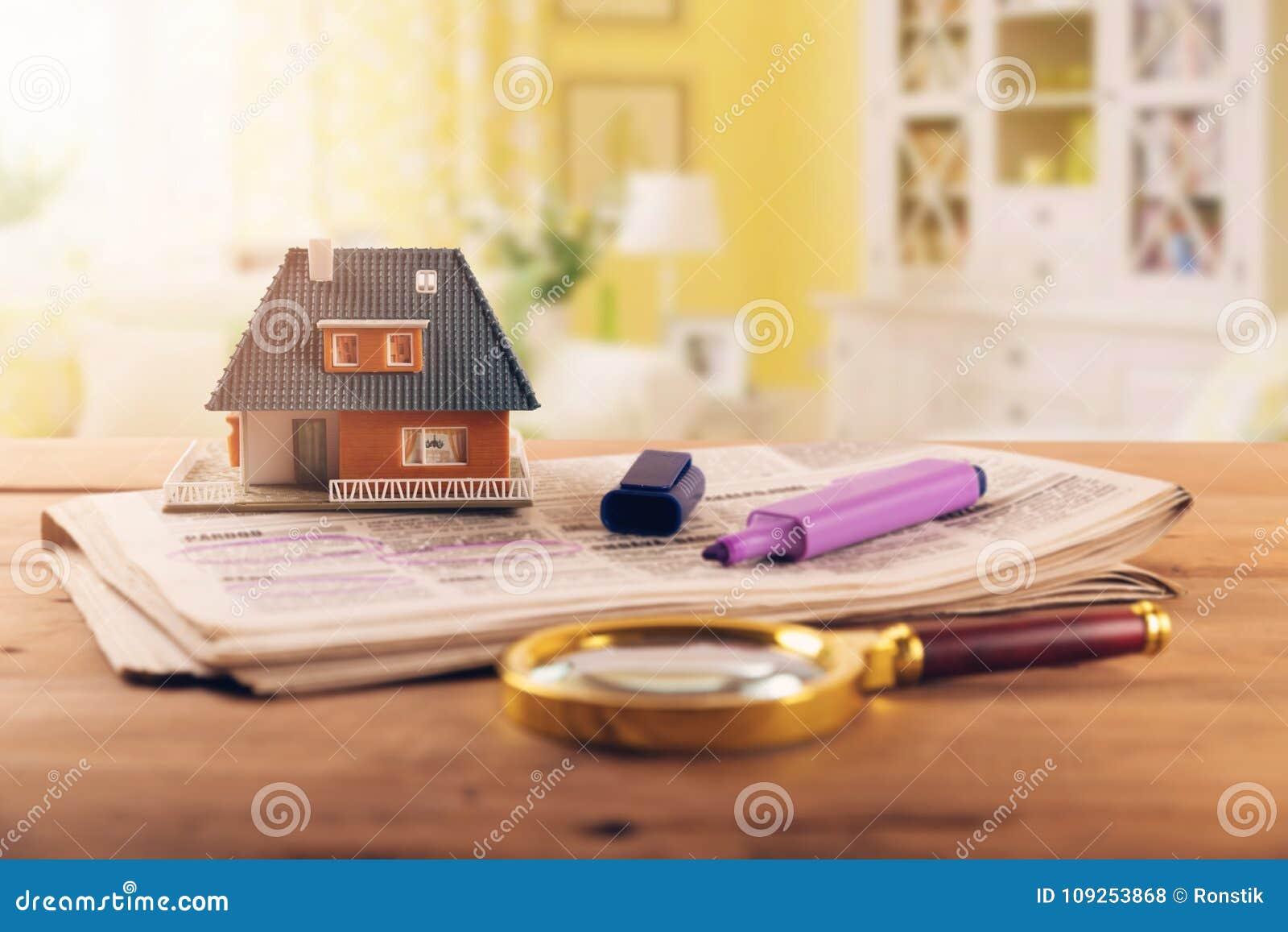 Suchen des neuen Hauses in den Immobilienkleinanzeigen der Zeitung