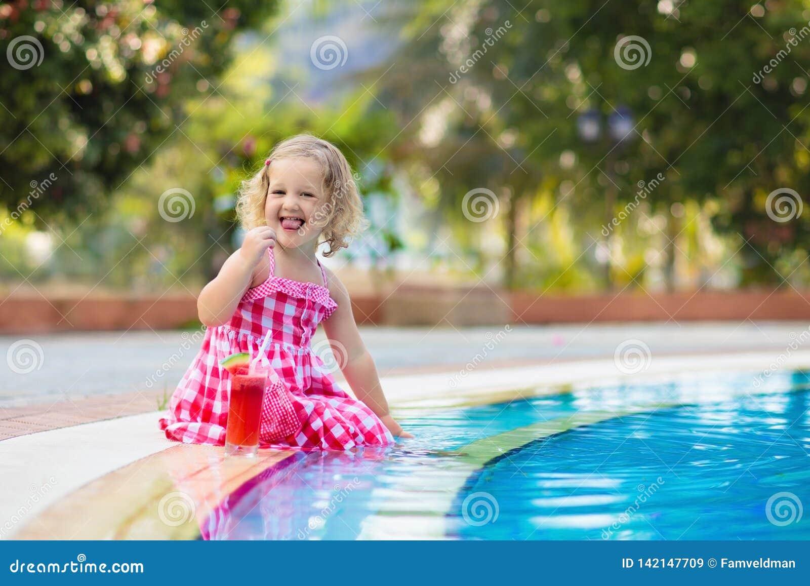 Suco bebendo da menina em uma piscina