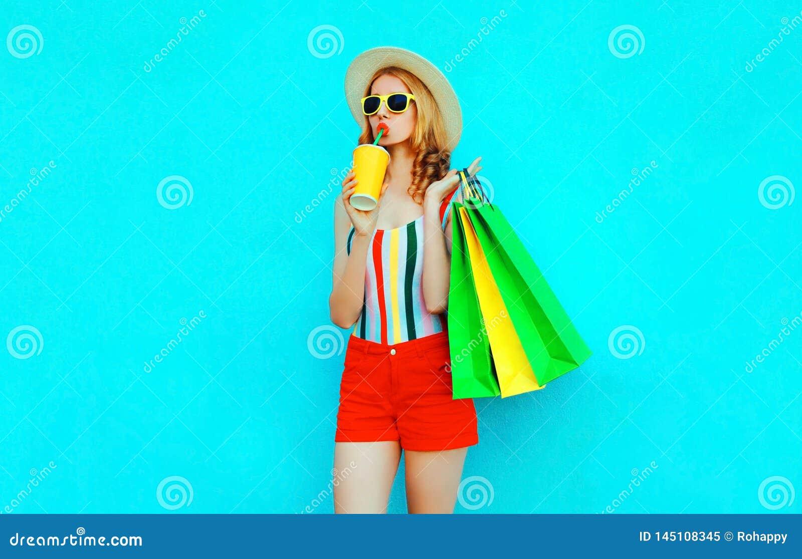 Suco bebendo da mulher à moda que guarda sacos de compras no t-shirt colorido, chapéu de palha do verão, óculos de sol, short