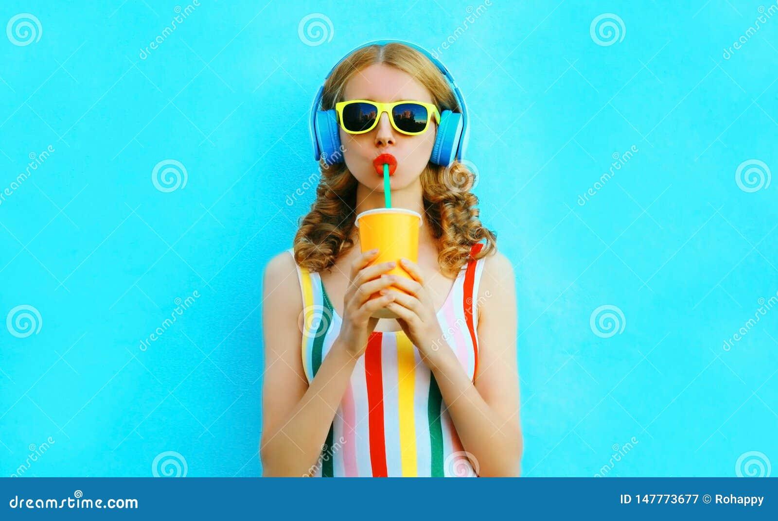 Suco de fruto bebendo da mulher à moda do retrato que escuta a música em fones de ouvido sem fio no azul colorido