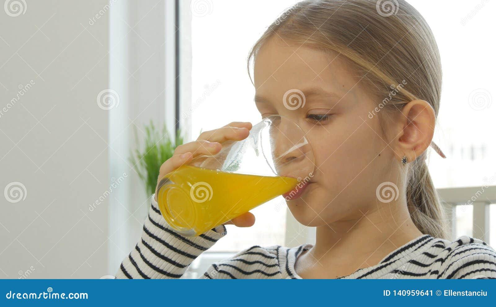 Suco de laranja bebendo da criança, criança no café da manhã na cozinha, limão da menina fresco