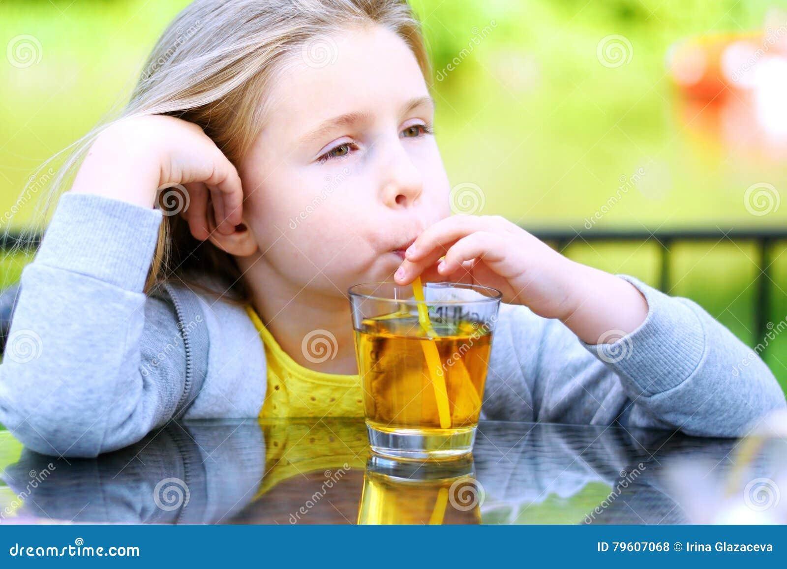 Suco de maçã bebendo da menina adorável no café