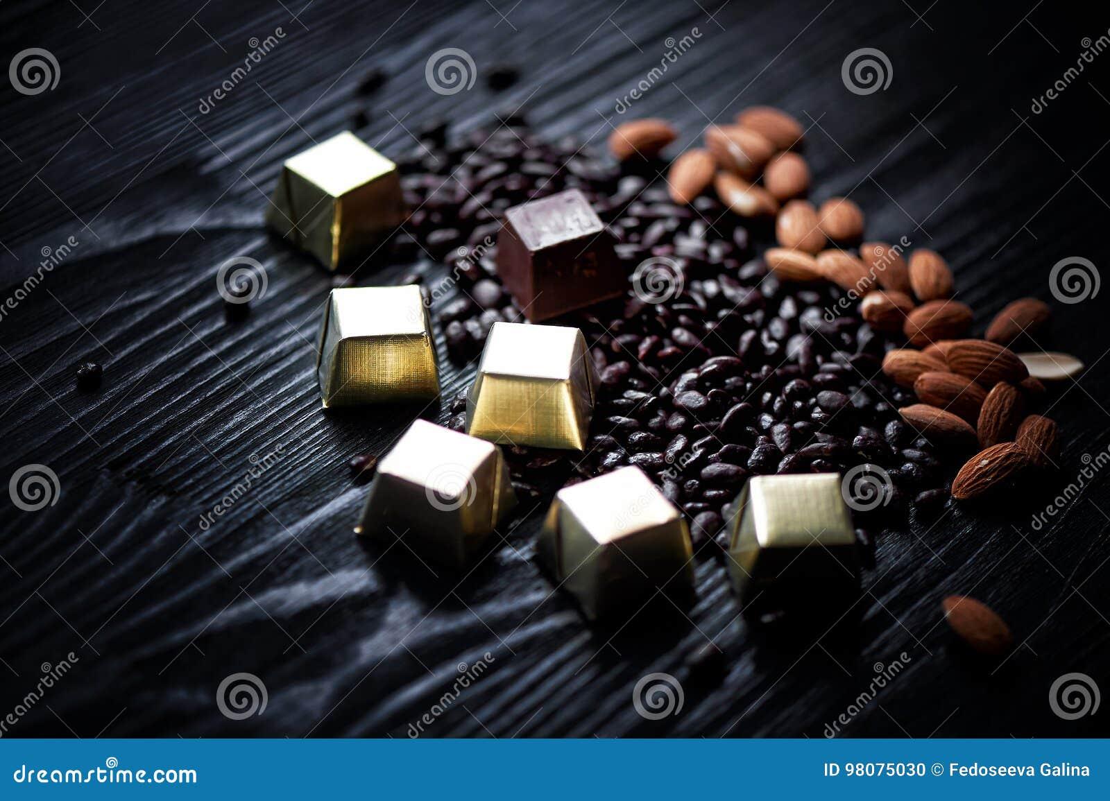 Sucrerie en aluminium, amandes et graines de tournesol d or en chocolat se trouvant sur un fond foncé studio