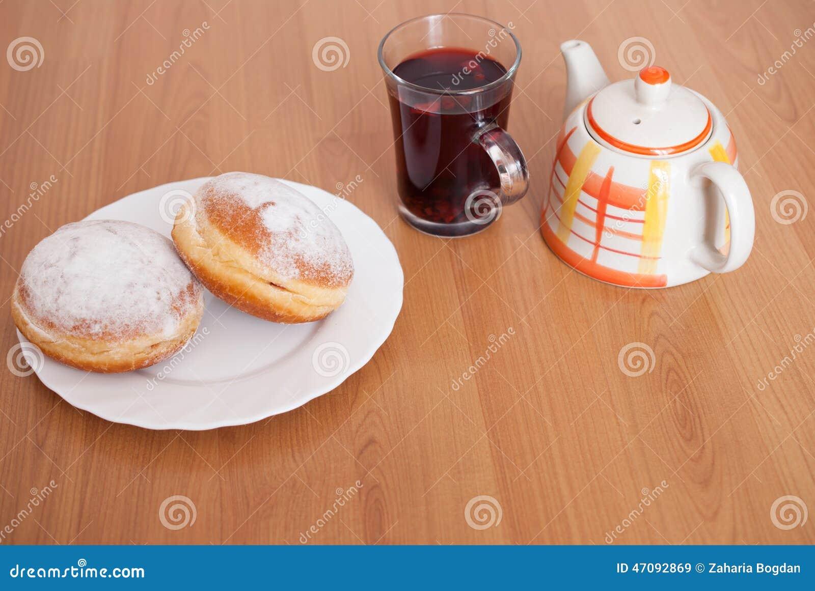 Sucrez les beignets enduits, un verre de thé de fruit et le pot de thé du plat blanc sur le fond en bois brun