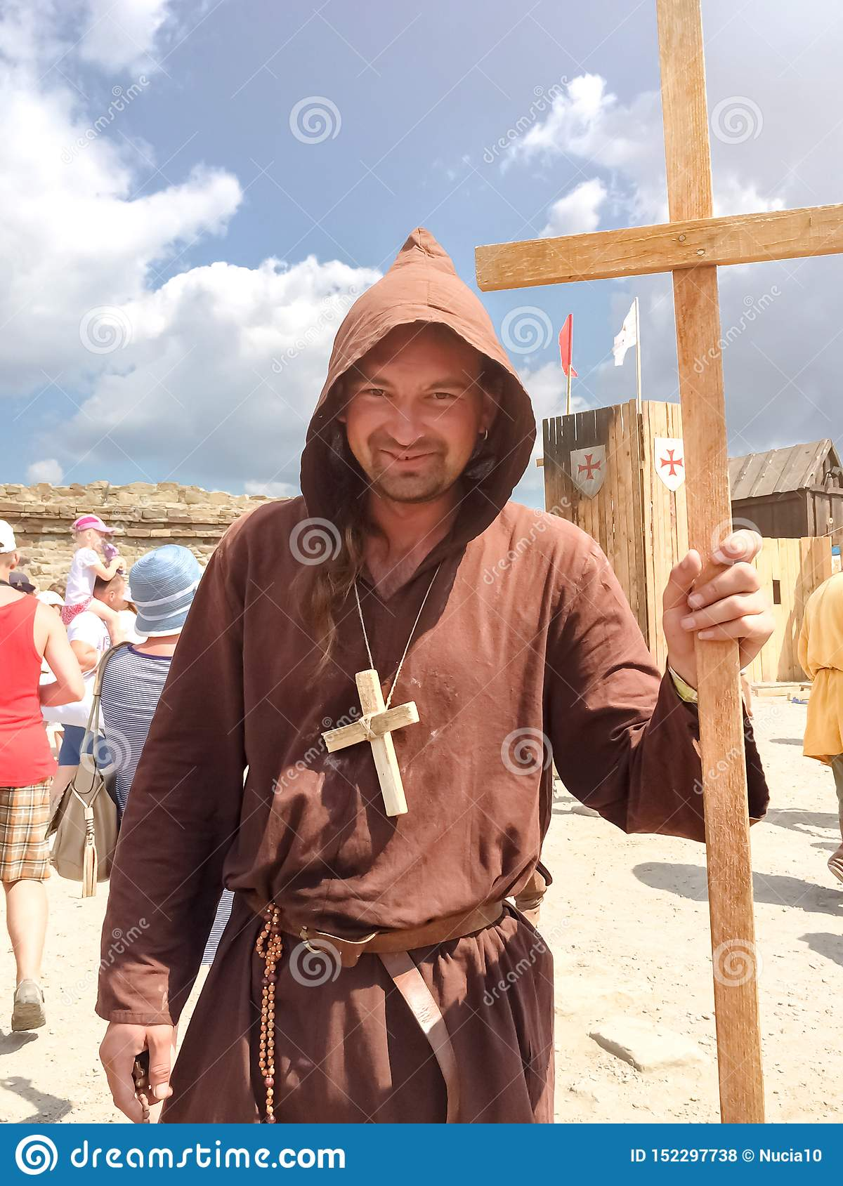 Sudak, Russia - August 16, 2015: man dressed as medieval priest, monk with a wooden cross with a staff in his hand and with a