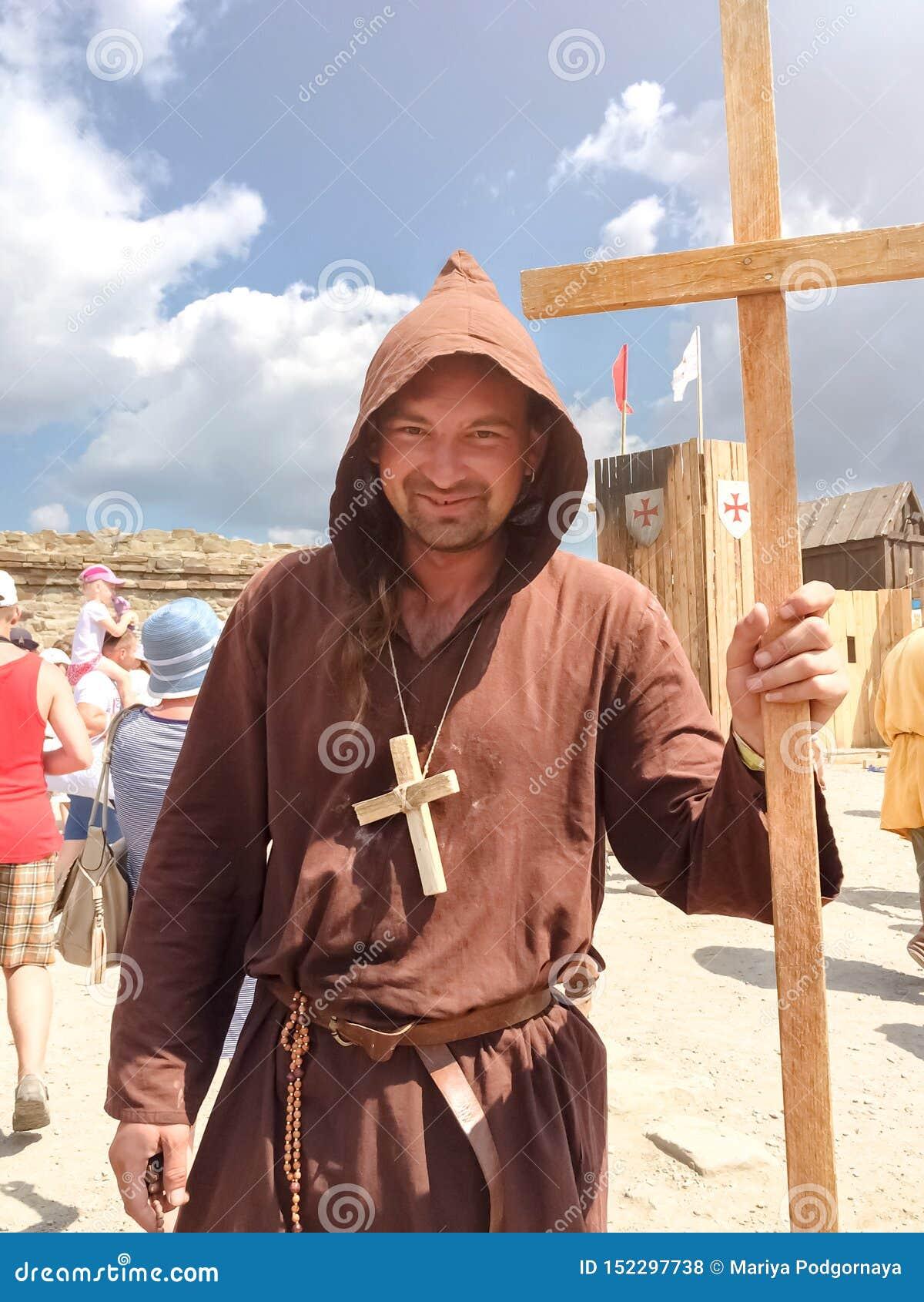 Sudak, Russland - 16. August 2015: Mann gekleidet als mittelalterlicher Priester, Mönch mit einem hölzernen Kreuz mit einem Perso