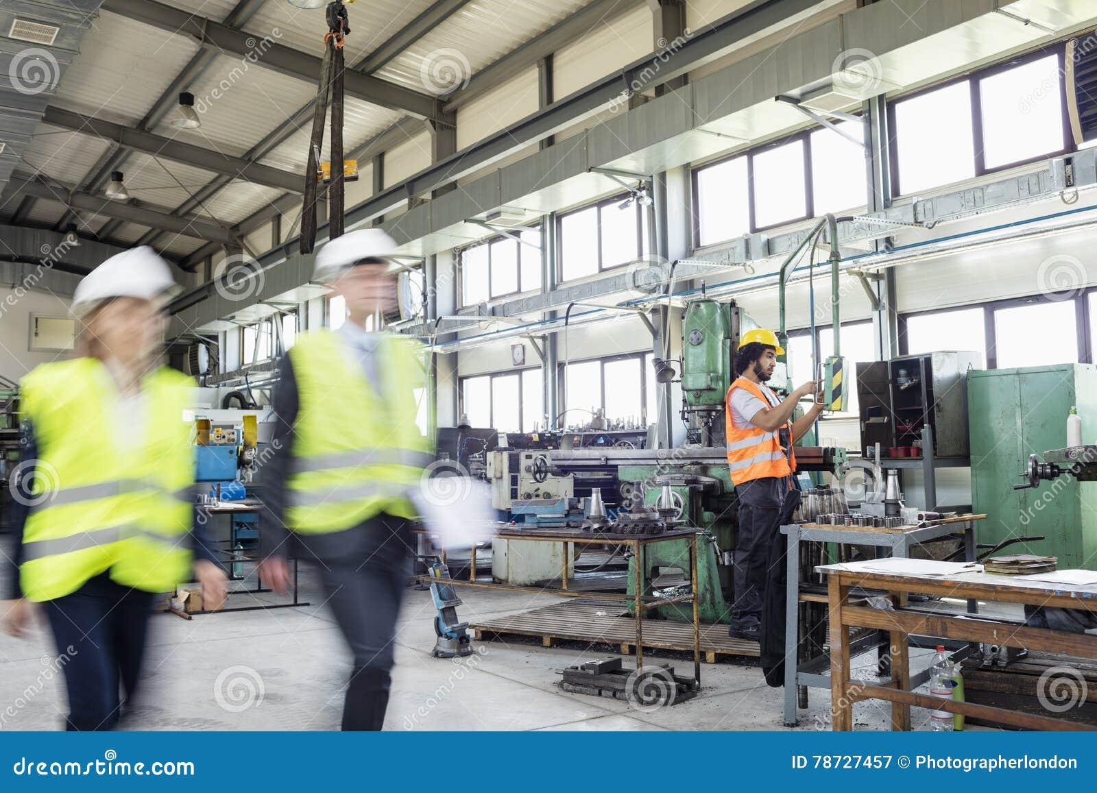 Suddig rörelse av affärsfolk med den manuella arbetaren i bakgrund på bransch