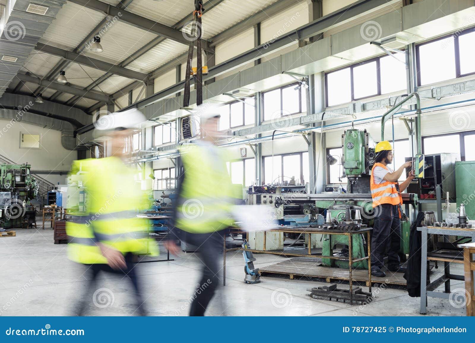 Suddig rörelse av affärsfolk som går med den manuella arbetaren i bakgrund på bransch