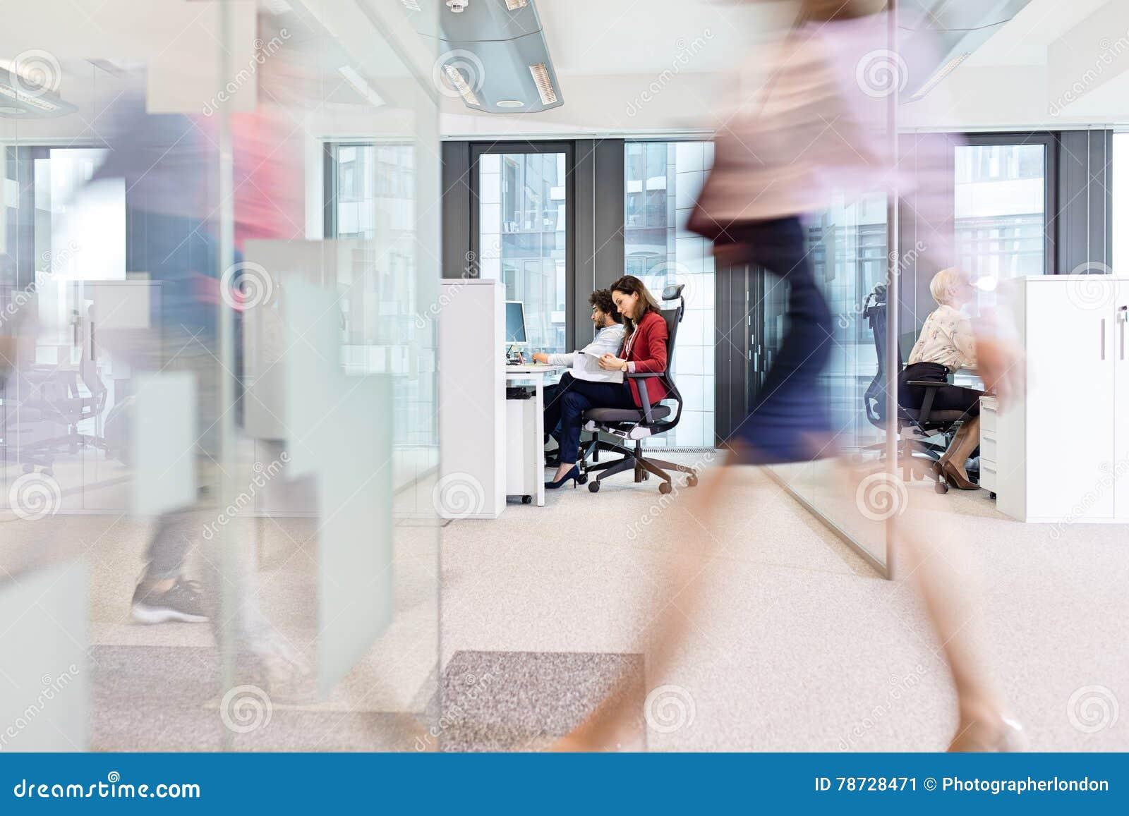 Suddig rörelse av affärskvinnan som går med kollegor som arbetar i bakgrund på kontoret