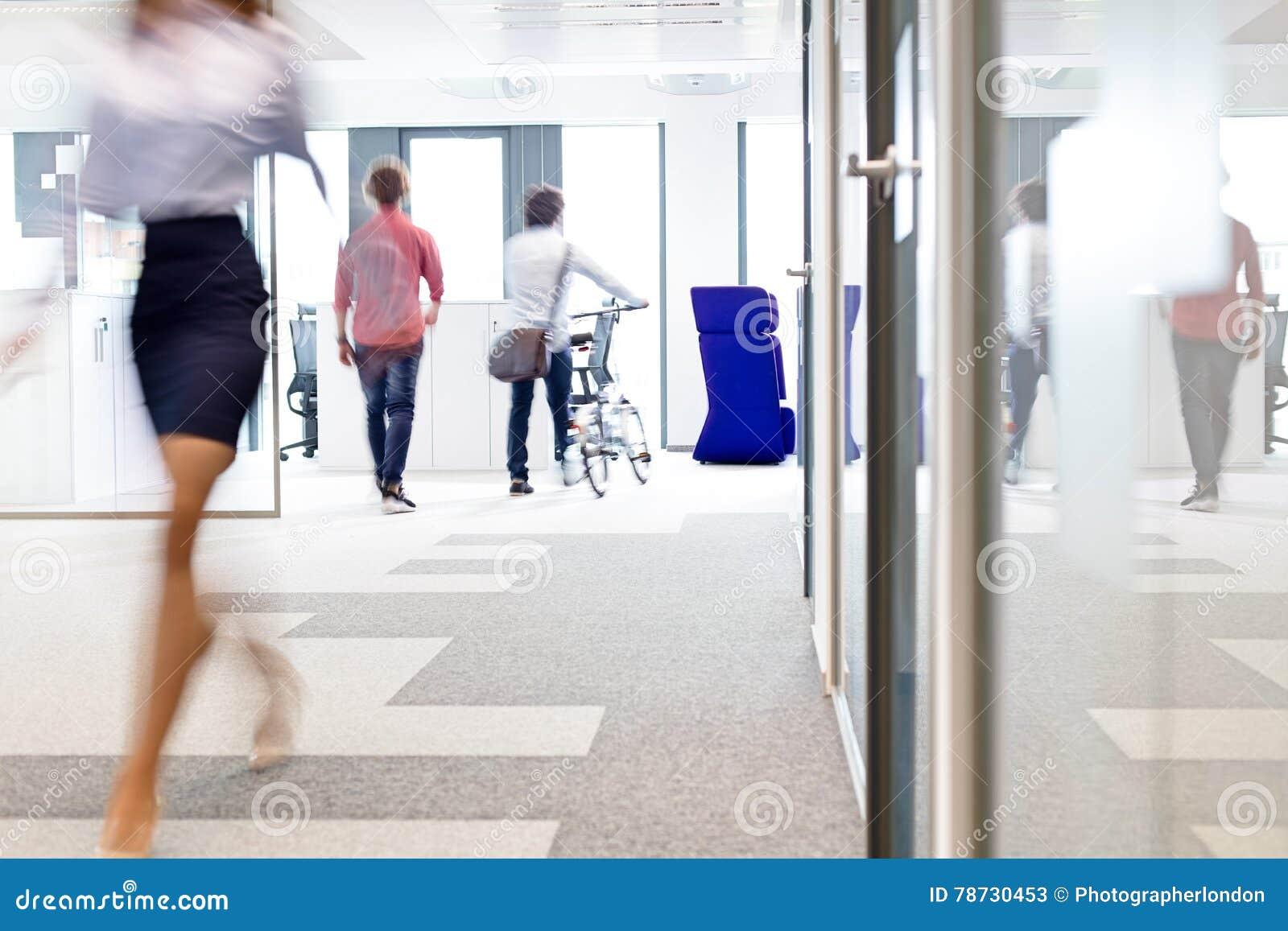 Suddig rörelse av affärskvinnan som går med manliga kollegor i bakgrund på kontoret