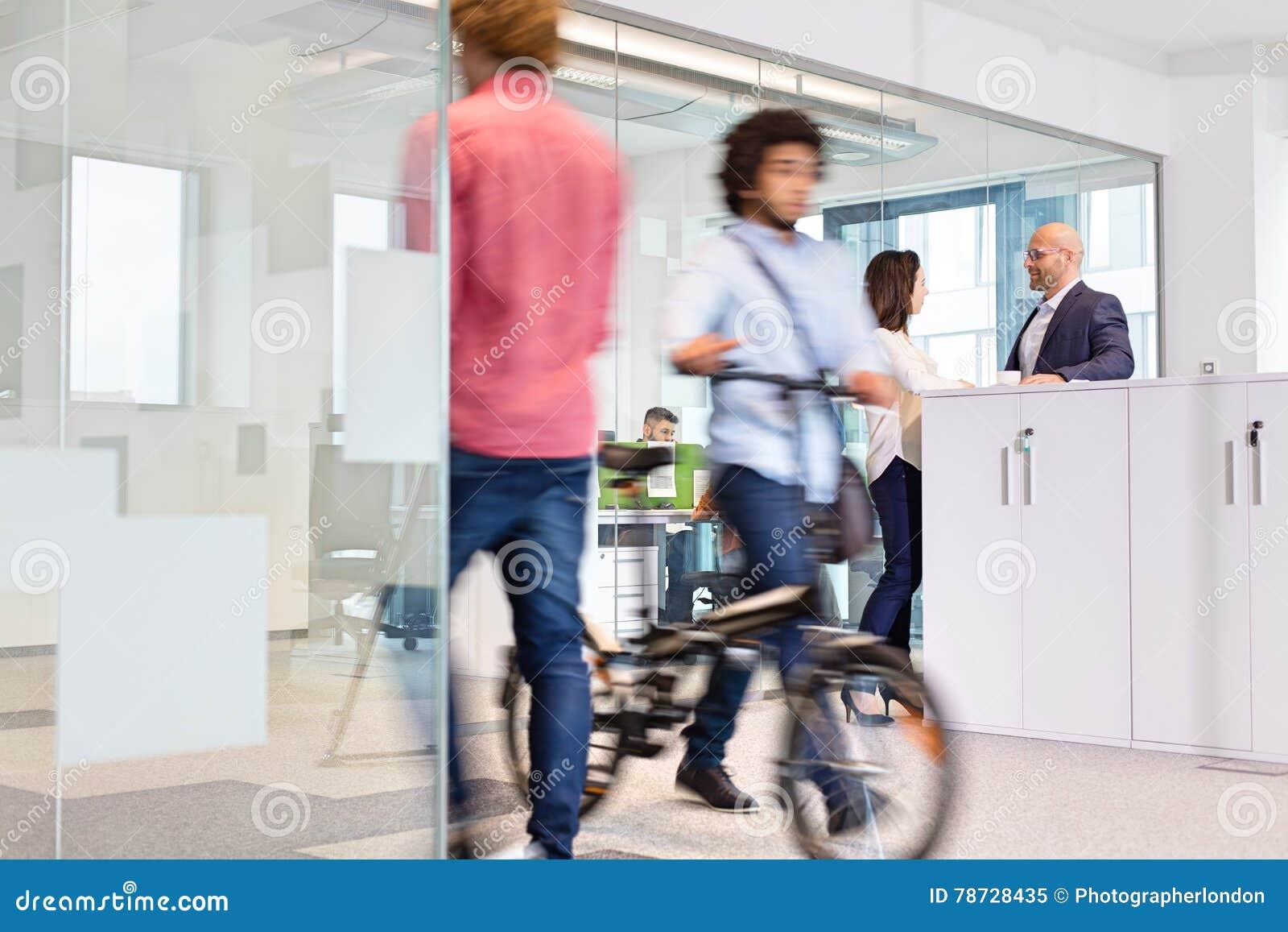 Suddig rörelse av kollegor med affärsfolk som diskuterar i bakgrund på kontoret
