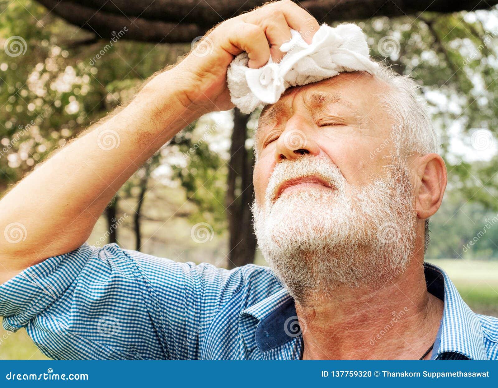 Sudor de barrido cansado con una toalla en el parque, concepto del hombre mayor de la atención sanitaria
