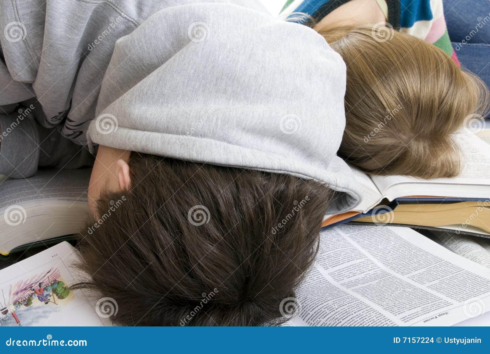 Sueño cansado de dos estudiantes en los libros