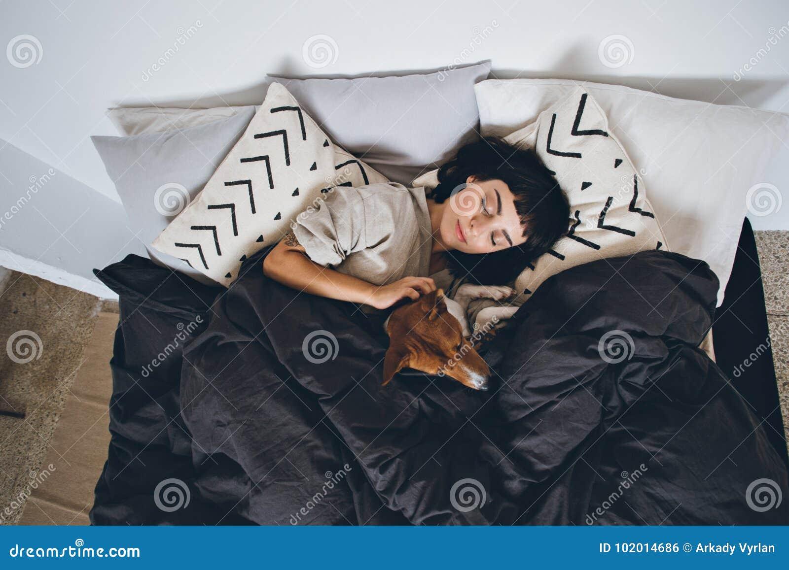 Sueño de la mujer y del perro en cama