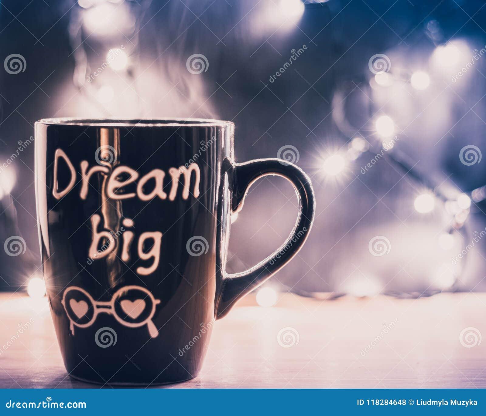 Sueño de la taza de café grande con vapor en un top de madera y luces de la Navidad en un fondo Copyspace