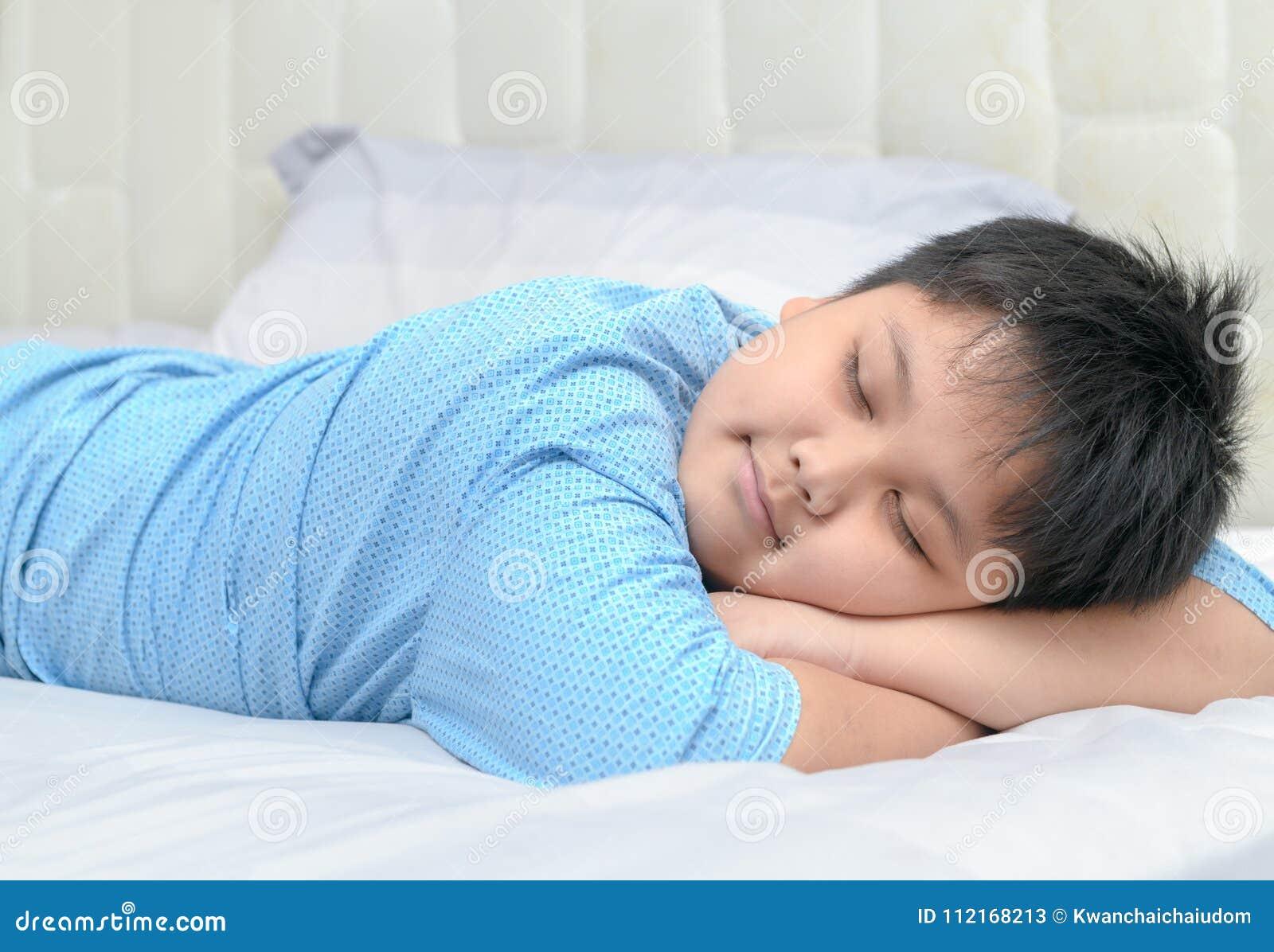 Sueño dulce del muchacho gordo obeso en su brazo