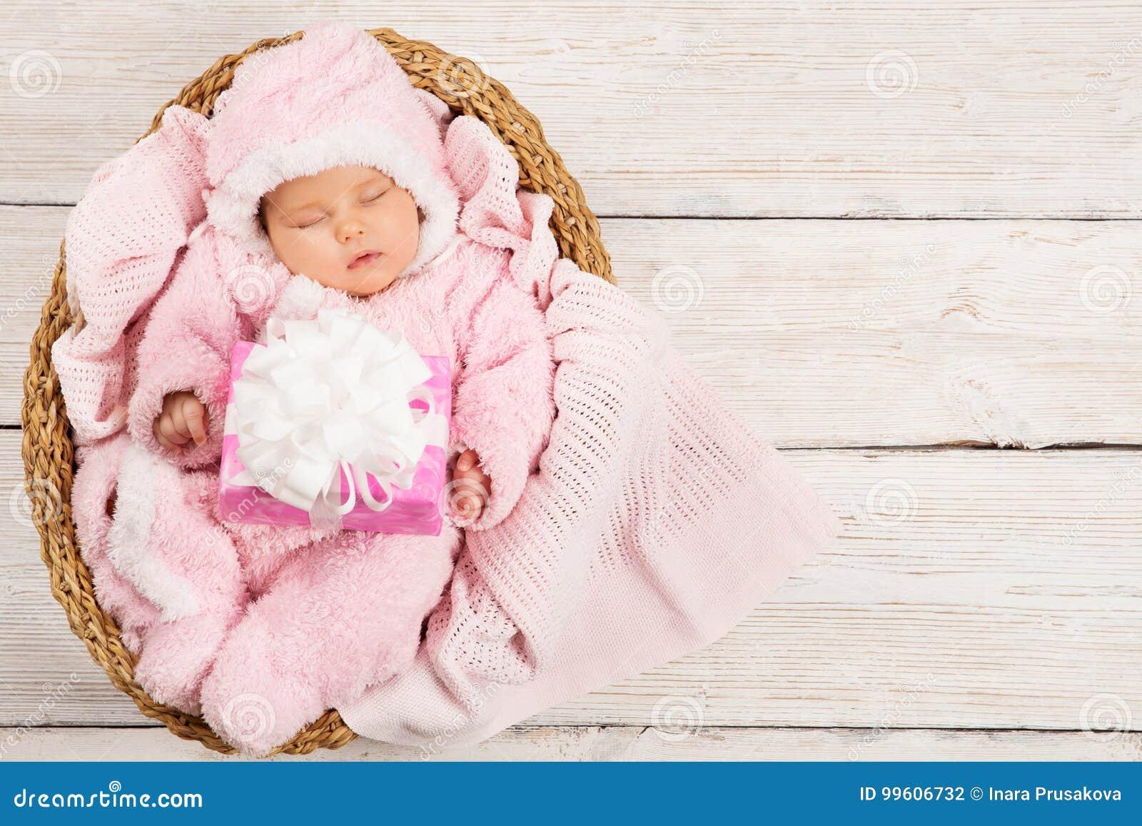 Sueño recién nacido del bebé con la actual caja de regalo, niño durmiente, rosa
