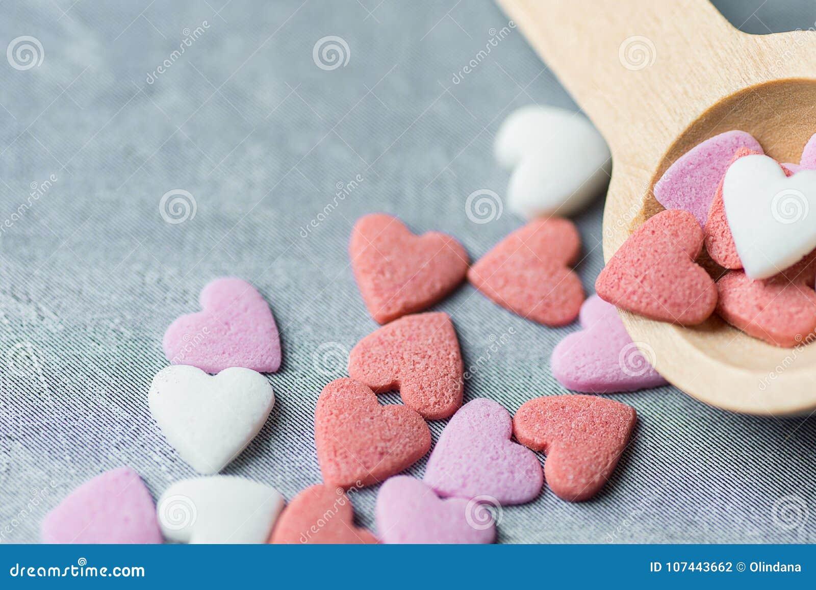 Sugar Sprinkles Candies Spilled blanco rosado colorido de la pequeña cuchara de madera en Grey Background valentines