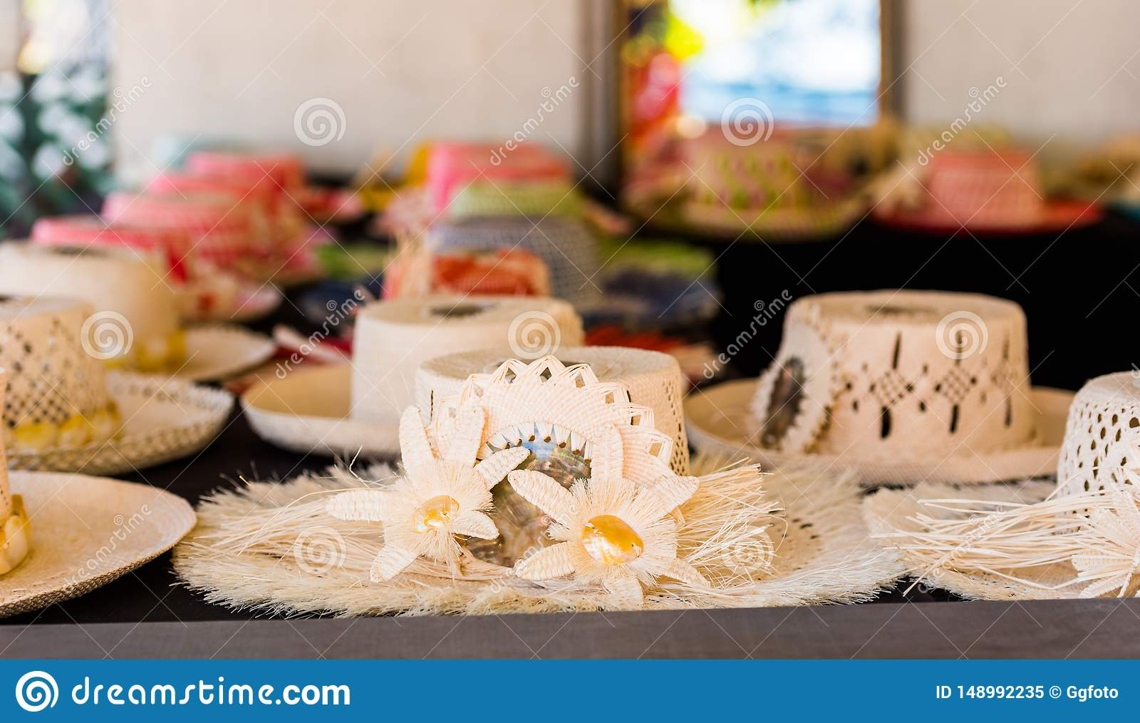 Sugrörhattar som är till salu i en tropisk souvenir, shoppar i Aitutaki, kocken Islands utomhus skjutit selektivt f?r fokus