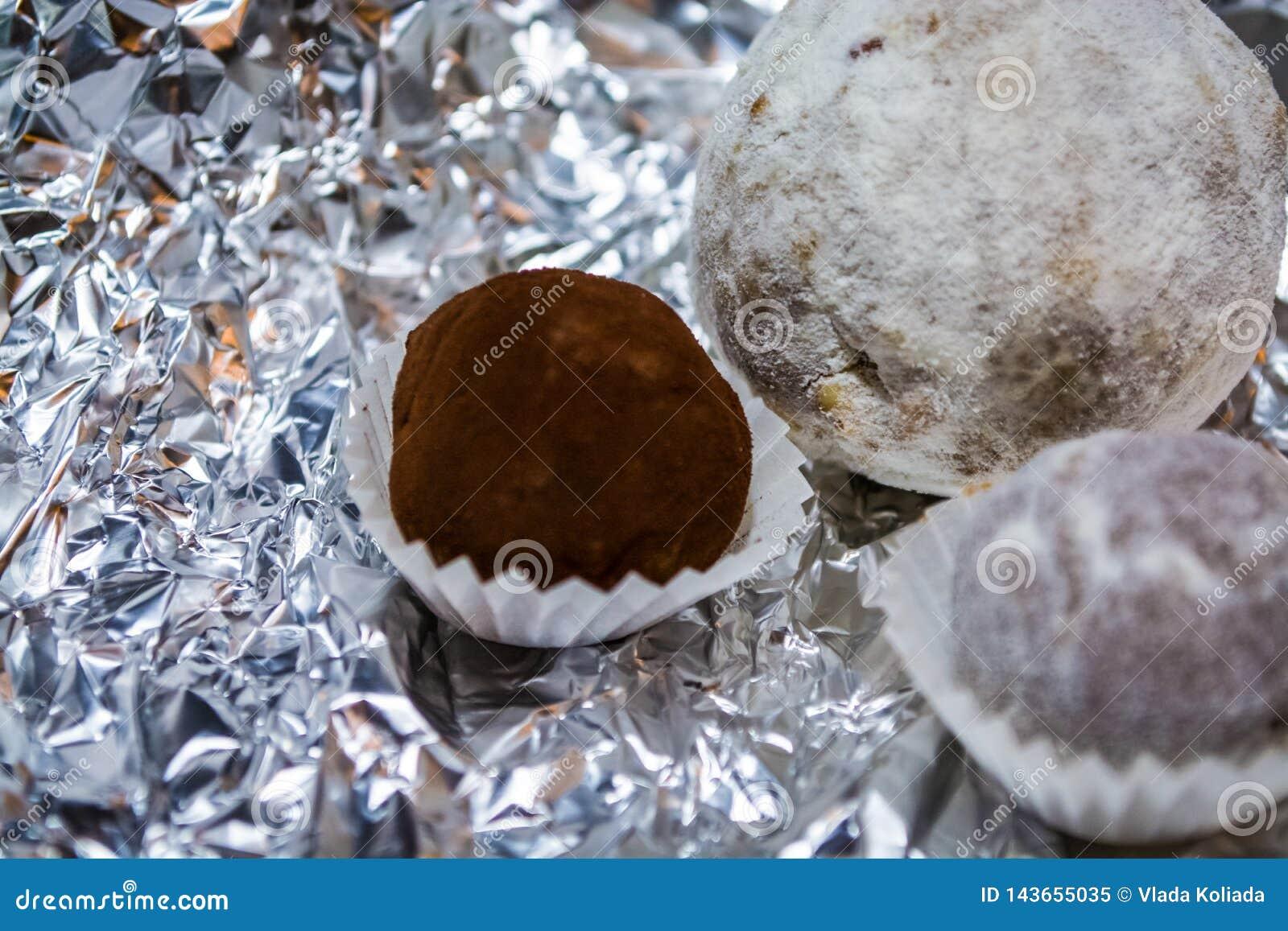 Suikergoed, smakelijk van natuurlijke chocolade, in de vorm van een bal Een hulpachtergrond van een folie Spel van licht en flard