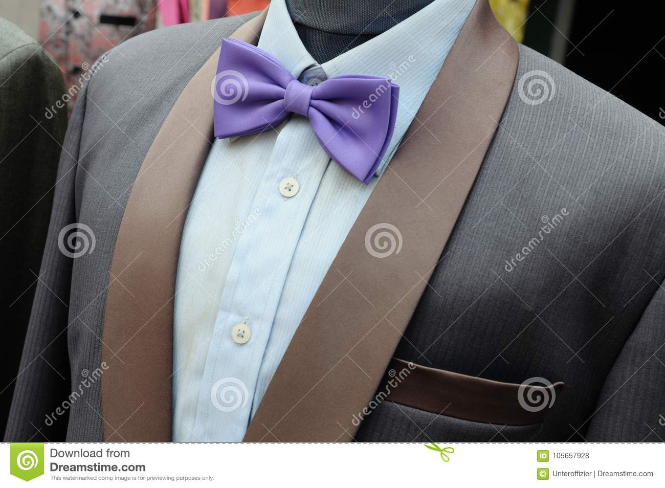 ba8f5d9bac74 Suit formal wear for men on a headless mannequins display. It has a purple  bow tie, dark grey suit and light blue shirt.